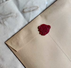 An envelope with a red wax seal embossed with the letter 'A' sits atop a pile of parchment